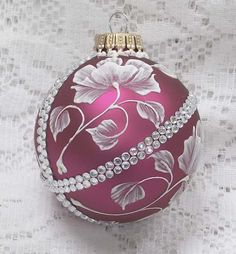 Margot Clark created this Dark Rose colored glass ornament with White 3D texture painted MUD floral design with added bling. Each ornament created is a one-of-a-kind. The texture medium and paint brush I use to paint the ornaments were both created to my specifications. My signature M is located on the bottom of the ornament. Gift boxed. Measures 2 1/2 x 2 1/2 Ornament weight is 2 ounces.