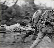 A wounded Marine is rushed from an Okinawa battlefield.
