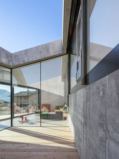 This robust concrete house in Savièse steps down the side of a hill and contains rooms lining internal patios that look out towards the nearby mountains.