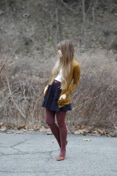 navy skirt, white t-shirt, mustard cardigan, maroon tights. Very sweet and put together.
