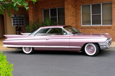 Pink Cadillac. Better pic of a 1961 Cadillac coupe than the white one elsewhere on the board. Note Cadillac's use of body color on the wheel covers. I recently saw a GMC with body-color accents on its' wheel spokes and thought of these great old Caddys.