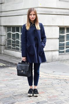 Coggles London Street Style with navy coat, black briefcase, indigo skinny jeans and black trainers.