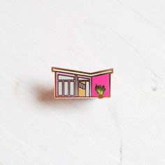 Our little version of a Palm Springs style mid-century house. Who wouldnt want to live in this cute pink house? Pair with our other Palm Springs inspired pins to bring a full on mid-century vibe to your denim jacket.  The pin measures 19mm x 9mm.