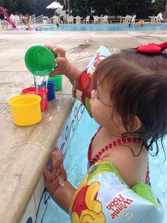 Transferindo água da piscina para os potinhos.