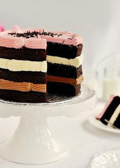 3 layers of rich Southern Devil's Food Cake stacked between fluffy Neapolitan flavoured Swiss Meringue Buttercreams: Belgian Chocolate, Vanilla, and Strawberry, and topped with pure dark chocolate sprinkles from Holland