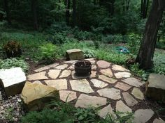 A custom made fire pit in the woods from www.landartcompanies.com