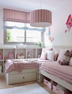 Habitación infantil con dos camas y una librería bajo la ventana