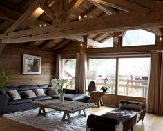 SWITZERLAND - This ski chalet living room decor is just what we'd want from a trip to the Swiss Alps! Lots of exposed wood and plush textures like leather and soft rugs. The ambient lighting helps warm the space, and the mismatched furnishings give it a lived-in, welcoming appeal.