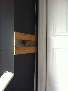 Be sure to paint the wall a dark color before putting your wood pallet boards up.  Some of it will show through.