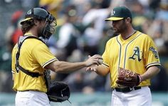 Oakland Athletics John Jaso, left, hands the game ball to pitcher Ryan Cook at the end of a baseball game against the Seattle Mariners, Thursday, April 4, 2013, in Oakland, Calif.