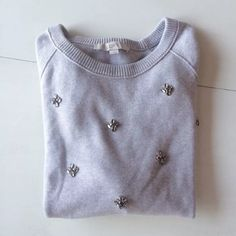 """Ann Taylor loft sweatshirt sweater Crewneck beaded This is a crewneck sweater by Ann Taylor Loft. It has embellishments on the front. They are darker gray and light pink rhinestones arranged in clusters. The fabric is light heather gray. Very soft and cozy, it's like a sweatshirt and sweater crossed, perfect for taking a casual look a step up. It is a size M. 50% cotton, 40% rayon, 10% silk. Hand wash, dry flat.   Shoulder to shoulder: 16.5""""-23"""" Arm pit to arm pit: 20""""-26"""" Waist: 18.5""""-26""""…"""