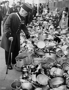 A Chelsea Pensioner adds a frying-pan to a heap of aluminium pots and pans at the WVS depot at Chelsea, following Lord Beaverbrook's appeal for aluminium for the war effort.