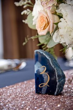 blue, pink & gold wedding table setting with blue and gold marble table numbers on a gold runner