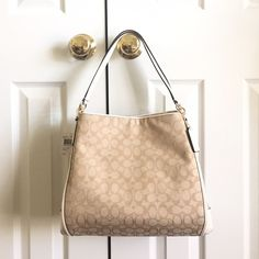 """Authentic Coach Outline Signature Phoebe Shoulder Authentic Coach Outline Signature Phoebe shoulder Bag signature canvas & leather. Style F36424. Color- Light Khaki/Chalk White with light gold hardware. New with tag. Dimensions- 13.75"""" L (bottom) or 11"""" L (top) x 10.75"""" H x 5.5"""" W & 8"""" handle drop height for shoulder wear. It has two compartments with zipper top in the middle (see picture), and has multiple inside pockets including a zip and slide pockets. It is a magnetic closure bag with…"""