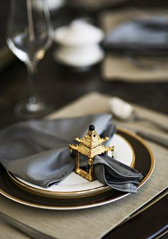 Miniature shrine napkin ring, silvery silky napkins, jet and gold rimmed china, muted but gently texture placemats, leather topped dining table [Frivolous Fabulous - Golden Napkin Rings]