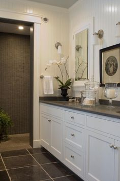 Beautiful white & gray bathroom design with white beadboard, white bathroom cabinets, gray corian counter tops, double sinks, white recessed mirrored medicine cabinets, brushed nickel sconces, gray marble tiles floor, orchid and gray glass tile shower surround.