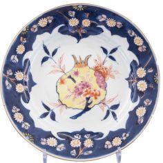 Assiette à décor d'une grenade éclatée en porcelaine de Chine de la Compagnie des Indes d'époque Yongzheng Décorée au centre d'une grenade sur une branche avec des fleurs plus petites et des feuillages. Le fruit, éclaté, révèle ses graines. Le motif central est laissé en réserve sur un fond blanc alors que l'aile est peinte d'un fond bleu, avec des branchages de chrysanthèmes en fleurs, dessinant quatre ruyi.