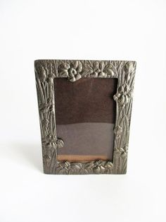 This pretty frame is made of Pewter etched with Iriss around the four front facing edge. It is a heavy frame. It is a table top frame with an easel back. It can be displayed vertically only. It has glass. The picture opening measures 3 x 4 1/2. Overall the frame measures 6 1/4 x 4 5/8. It is in Vintage Picture Frames, Vintage Pictures, Quilting Hoops, Pewter Metal, Iris Flowers, Emboss, A Table, Frame Gallery, Display