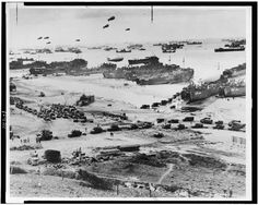 Bird's-eye view of landing craft, barrage balloons, and allied troops landing in Normandy, France on D-Day.