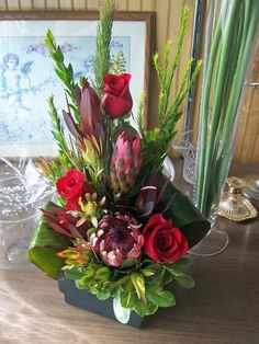 Proteas, red roses, in a tropical arrangement. Red Roses, Floral Arrangements, Tropical, Elegant, Flowers, Plants, Gifts, Rose Flower Arrangements, Classy