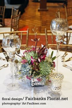 Succulents, Orchids, Fern Curls, Scabiosa, Wax Flower, Seeded Eucalyptus, Safari Sunset and mercury Glass candle holders make a lovely wedding reception table arrangement, designed by Lana with Fairbanks Florist, Photographed by Art Faulkner.com
