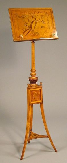An Antique Nineteenth Century Music Stand by Howard & Sons of Berners Street London Constructed in Satinwood, extensively inlaid, the tripod footed base of outswept tapering form, with a patera inlaid platform, supporting a triangulated box centre, with masks inlaid, and knopped angles, the central column adjustable, the music tablet inlaid with a tambourine, pipes, and other devices. The base having an ivorine plaque with the makers detail