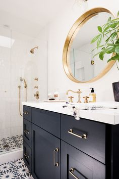 White walls, floral tiled floors, black drawers, gold faucets, and gold framed circular mirror