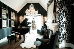 Oh my god! We spotted this interior designed by Charles Neal and did a double take! A baby grand with a tufted piano bench, black striped wall paper, white and black ornate wall paper to offset it, studded chairs, fur rug, crystal chandelier, the list goes on and on! We're in love!