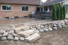 Boulder wall and patio By All Natural Landscapes
