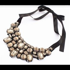 NewDream A-little Dream Bib Necklace Beautiful champagne crystals are placed in abstract rows to create this unique bib necklace Ties on with a black satin ribbon. 15-18 inches in length. Jewelry Necklaces