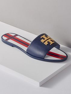 This leather slide by Tory Burch is fashioned with a gleaming logo and a striped footbed.