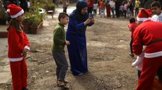 A Syrian refugee from Aleppo takes a picture of her son posing with a Lebanese volunteer dressed as Santa Claus  #syria #aleppo #photography #refugee #camp #christmas #2016 #history #politics