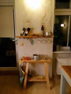 Wooden rack in Berlin apartment. Made of one piece of ash wood. It contains four bottles and six glasses. Fits in perfectly with raw, creative space.