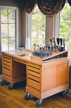 Not all work from home jobs involve typing on a computer. For those in a creative field, this desk set up is an absolute dream. Consider reorganizing your space with shallow drawers for your paint and a nifty brush holder. | Wonder Forest | Home Decor | Cute Home Office Ideas | Home Office Inspiration | Painting Station