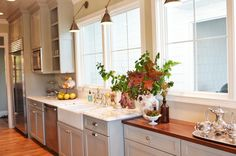 Gorgeous kitchen design with gray kitchen cabinets painted Benjamin Moore Fieldstone, farmhouse sink, calcutta gold marble countertops, custom buffet cabinet with walnut butcher block countertop, Visual Comfort Boston Library Sconces and Restoration Hardware Gilmore knobs & pulls in polished nickel.