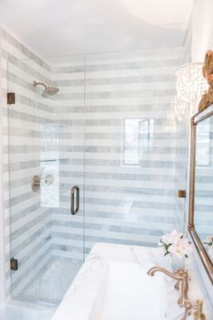 beautiful bath room. love the gold faucet, striped tile pattern and glass shower door