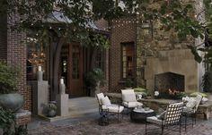 Brick exterior, natural stone fireplace, string lighting, brick patio | Darden Design Group