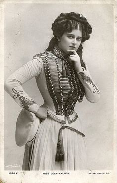 1900s vintage postcard of Scottish actress and singer, Miss Jean Aylwin. Military style embroidery (with cords), trimmings on the bodice, jacket. Interesting Victorian fashion details. I believe this military style was quite fashionable during the 1880s.