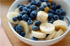 a bowl of cereal with bananas & blueberries.