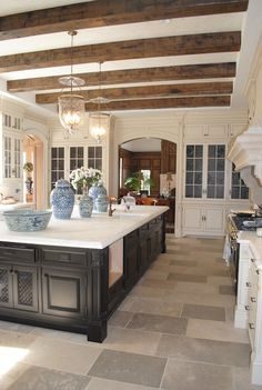 French two-tone kitchen design with rustic box beams, ebony stained kitchen island, ivory glass-front kitchen cabinets, calcutta marble countertops, sink in kitchen island, glass lanterns and ming ginger jars.