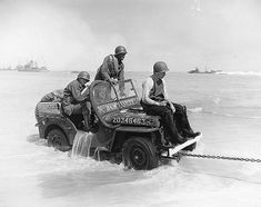 Normandy, France 1944 - Jeep being towed out of the ocean.