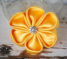 Buttery Gold is a golden yellow satin cherry blossom style flower with a rhinestone center. Elegant & simple, this accessory is great for holidays, weddings, or year-round wear! This hair accessory is secured to an alligator clip for easy wear in the hair, or clipped to a purse or lapel.