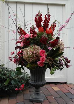 Rich jewel tones In this large arrangement of antique hydrangea, pink garden roses, purple mini calla lilies, burgundy snapdragons, protea, and pink flowering branches.