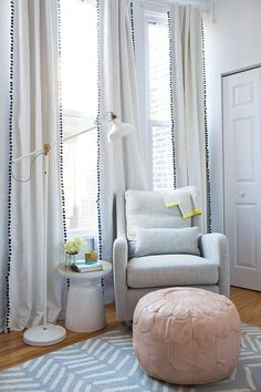 Chic boy's nursery features a gray glider, Land of Nod Milo Glider, next to a West Elm Martini Side Table and a pale pink Moroccan pouf, Lulu & Georgia Salma Moroccan Pouf, atop a CB2 Hash Looped Rug illuminated by an Ikea Ranarp Floor Lamp placed in front of windows dressed in white curtains accented with black pom pom trim, PB Teen Pom Pom Blackout Drapes.