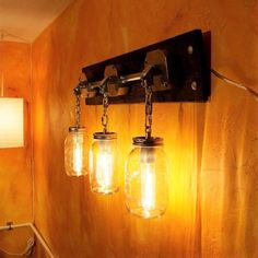 """Industrial hardware and conduit artfully assembled to create this unique Mason Jar sconce light. -- """"JARS OF LIGHT""""-- A rustic Industrial triple light wall fixture. Industrial Mason Jar light sconce or rustic vanity light, Handcrafted w/ Pipe, exposed conduit, reclaimed Wood"""