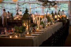 These wedding lanterns are displayed with small green potted plants. An eco-friendly centerpiece and beautiful.