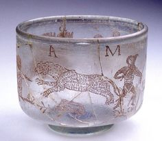 Roman inscribed glass circus cup, 3rd century A.D. This glass shows a battle between a Retarius called Pulcher and a Secutor called Auriga, it also shows a battle between a Venator and a leopard and two wrestlers called Hercules and Antaios.