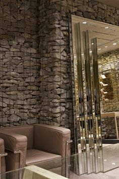 At the Belo Horizonte retail location for Brazilian shoe brand Luiza Barcelos, designer Pedro Lazaro has used rocks contained within metal cages to define areas within the store.