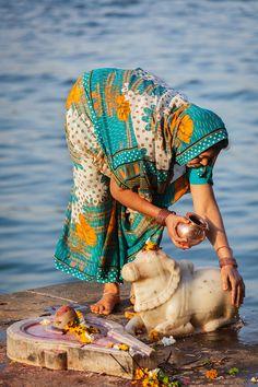 MAHESHWAR, INDIA - APRIL 26: Indian woman performs morning pooja on sacred river Narmada ghats on April 26, 2011 in Maheshwar, Madhya Pradesh, India. To Hindus Narmada is one of 5 holy rivers of India