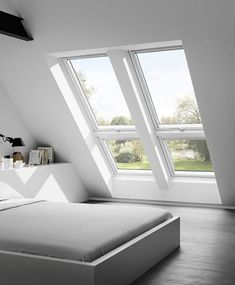 White room with large, leaning window.